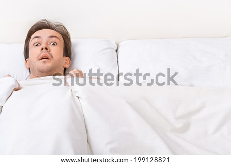 Young man lies in the bad and looks at camera with scared view - stock photo