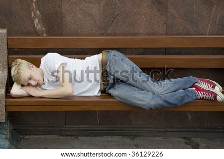Young man lies on a bench in park