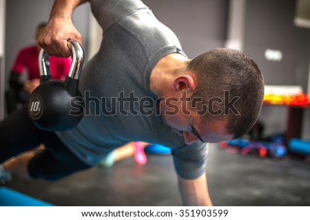 Young man lifting dumbbell and kettlebell at the fitness center - stock photo