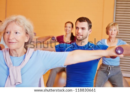 Young man lifting dumbbells in back training class in gym - stock photo