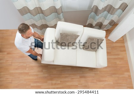Young Man Lifting Sofa In Living Room - stock photo