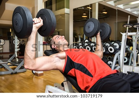 Young man lifting weights in the gym - stock photo