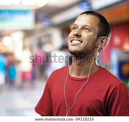 young man listen to music at shopping center - stock photo