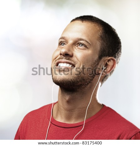 young man listen to music on a lights background - stock photo