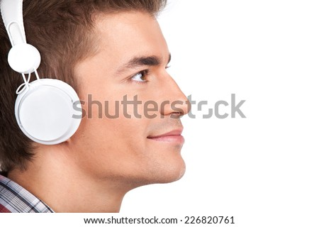 Young man listening headphones on white background. closeup picture of profile of guy looking up in headphones - stock photo
