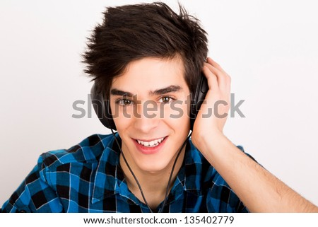 Young man listening music with headphones at home - stock photo