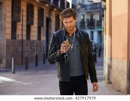 Young man listening music with smartphone earphones walking in the street - stock photo