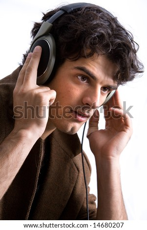 Young man listening to headphones in deep concentration with white studio background.