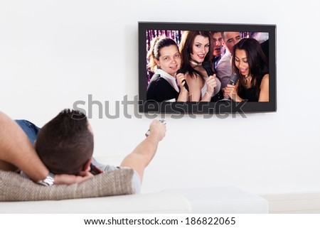 Young man listening to karaoke on TV in living room
