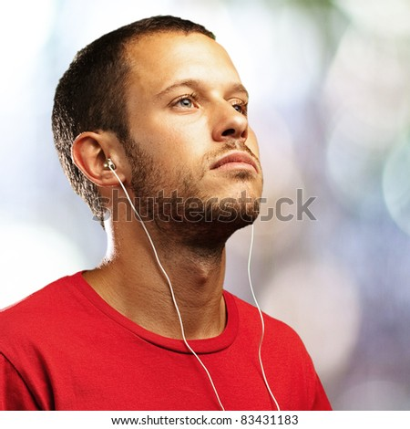 young man listening to music against a city lights background - stock photo