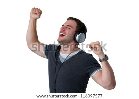 Young Man Listening to music and dancing with arms in air