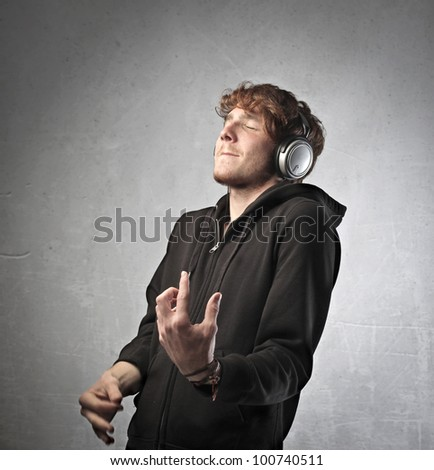 Young man listening to music and playing air guitar - stock photo
