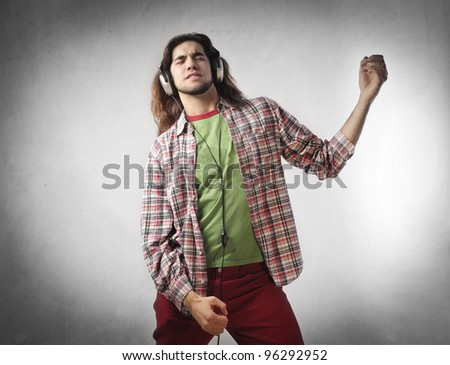 Young man listening to music and playing air guitar