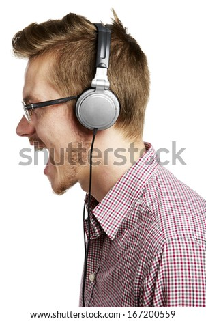 Young man listening to music and singing with headphones. Isolated on white.  - stock photo