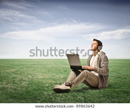 Young man listening to music from his laptop on a green meadow - stock photo