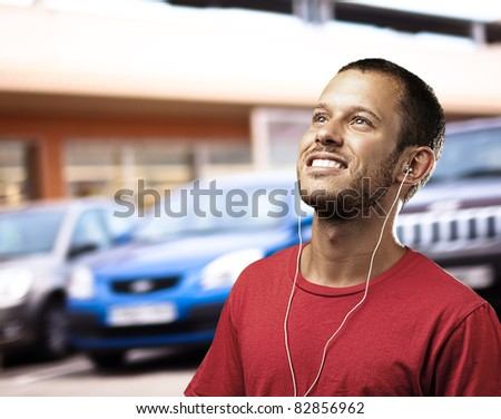young man listening to music in the street - stock photo