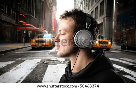 Young man listening to music on a city street - stock photo