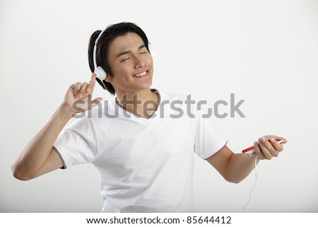 Young man listening to music on an smart phone - stock photo