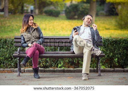 Young man listening to music on his smart phone and singing while woman sitting on the same park bench trying to use her phone - stock photo