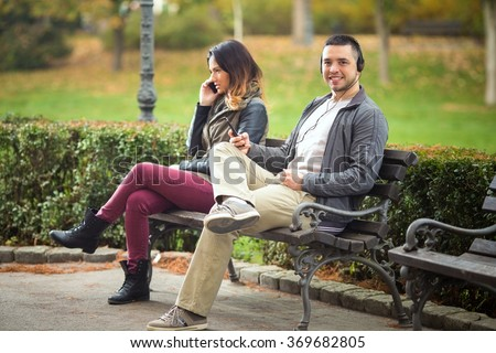 Young man listening to music while woman sitting on the same park bench is talking on the phone - stock photo