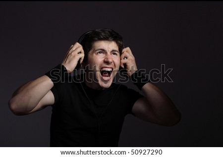Young Man listening to music with headphones on dark background - stock photo