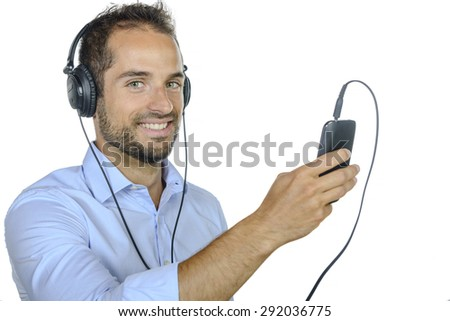 young man listening to music with his phone on white background - stock photo