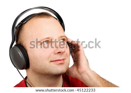 Young man listening to the music in headphones isolated on white