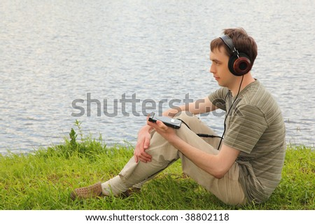 Young man listens music in headphones sits on grass ashore