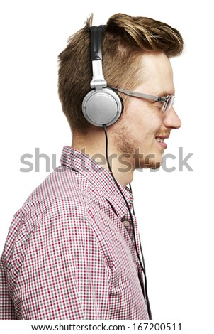 Young man listens to music and smiles with headphones. - stock photo