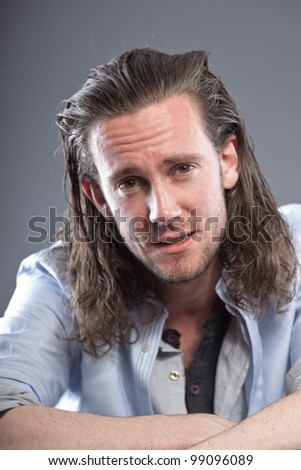 Young man long hair with expressive face wearing blue shirt. Isolated on grey background.