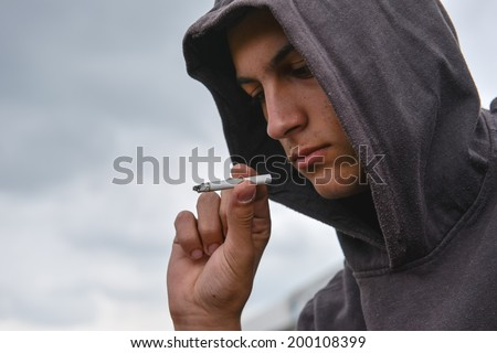 Young man looked at the cigarette and is undecided whether to smoke or not - stock photo