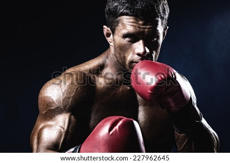 Young man looking aggressive with boxing gloves. Caucasian male model isolated on dark background. - stock photo