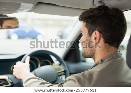 Young man looking ahead while driving in his car - stock photo