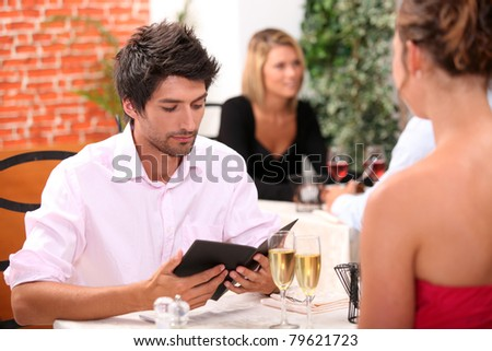 Young man looking at a menu in a restaurant - stock photo