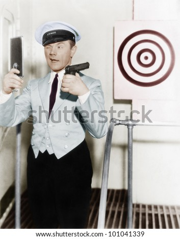 Young man looking at a mirror and aiming at a dartboard with a handgun - stock photo