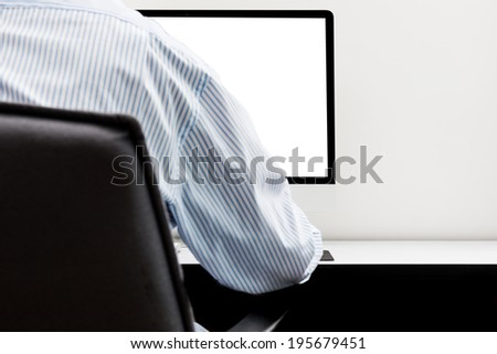 Young man looking at empty computer screen, back view - stock photo