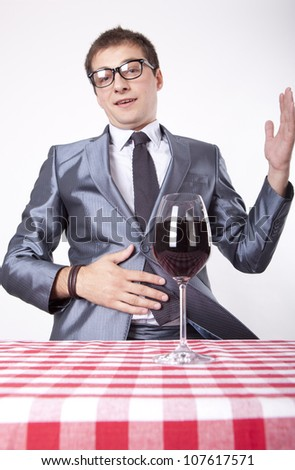 Young man looking at glass of wine. - stock photo