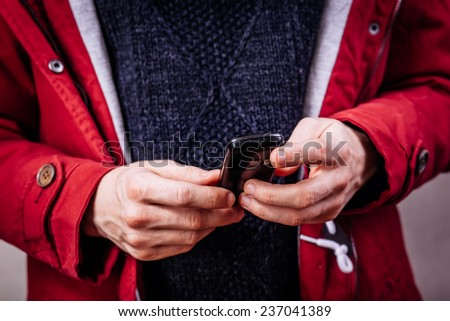 young man looking at his smart phone while text messaging - stock photo