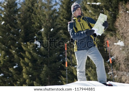 Young man looking at map, while walking with snow shoes