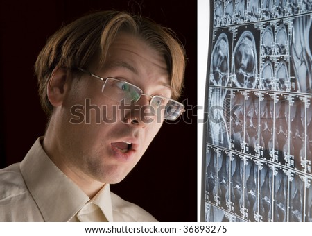 Young man looking at MRI film in horror - stock photo