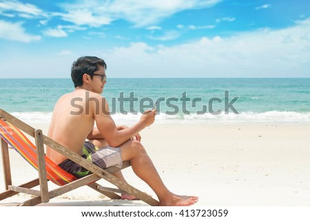 young man looking at news and messaging on his smart phone at beach - stock photo