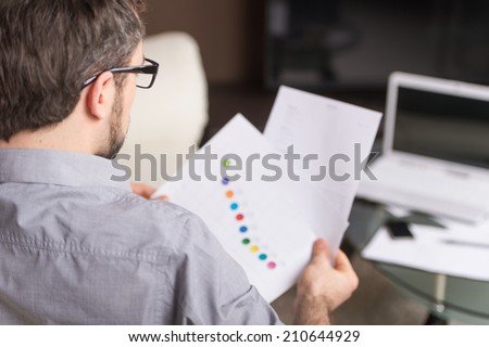 young man looking at paper in glasses. over shoulder view of man sitting on sofa and holding documents - stock photo