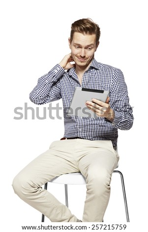 Young man looking at the tablet and thinking. - stock photo
