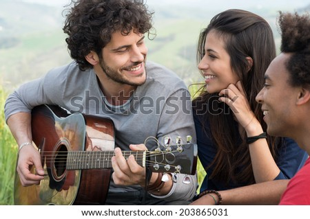 Young Man Looking At Woman While Playing Guitar Outdoor - stock photo
