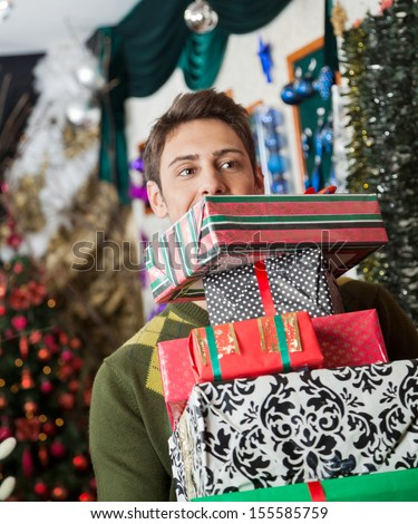 Young man looking away while carrying stacked Christmas gifts in store - stock photo
