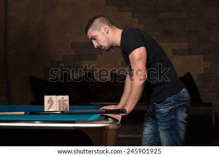 Young Man Looking Confused At Billiard Table - He Is Losing - stock photo