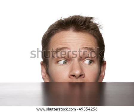 young man looking from behind a table - stock photo