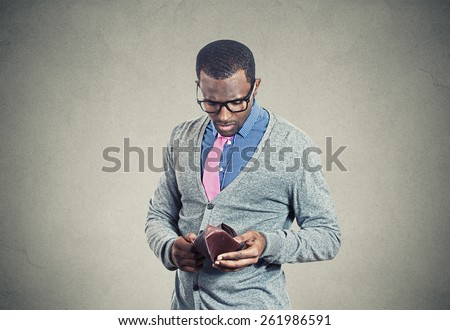 Young man looking into his empty wallet has no money  - stock photo