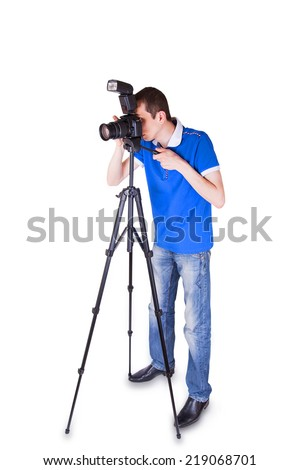 Young man looking into the camera on a tripod isolated on white background - stock photo