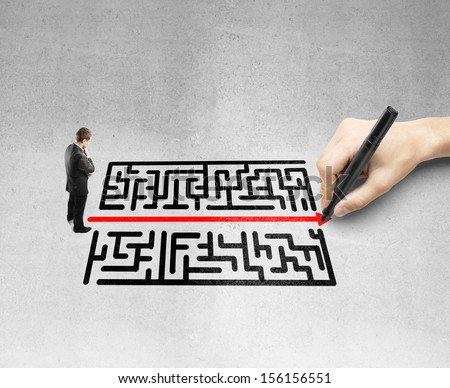 young man looking like a hand drawing a maze - stock photo